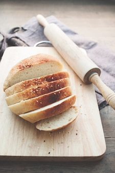 Loaf of bread on wood background with bakery tools, food concept