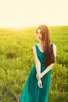Lonely girl on the meadow at sunset