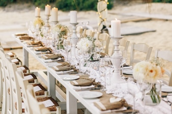 Long dinner table decorated with flaxen cloth and white candles