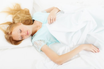 Long-haired girl in nightshirt sleeping on white sheet