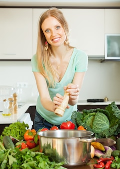 Long-haired woman adding spices to the pot