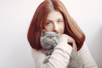 Long-haired young woman holding her cat