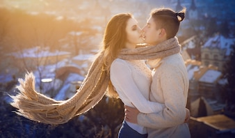 Long scarf envelopes young couple kissing on the hill in rays of warm morning sun