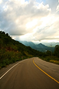 Long straight road go to the mountain and sky