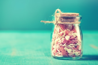 Love concept with jars on a turquoise background, pastel toning.