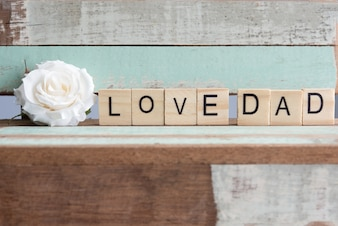 Love dad words with white rose on rustic vintage table