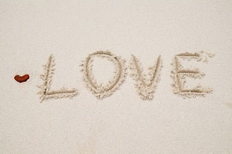 Love written on beach white sand.Vintage tone,retro filter effect,Soft focus,Low light.(selective focus)