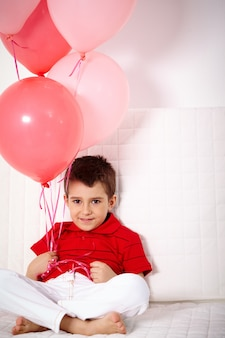 Lovely child holding balloons