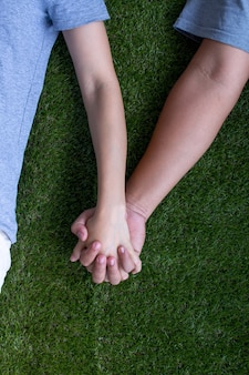 Lovers couple holding hands stay on green artificial grass valentines concept