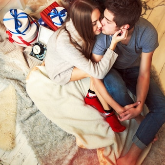 Loving couple kissing with many gifts