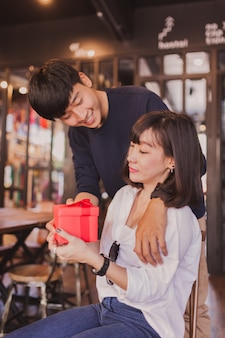 Loving couple smiling while the girl holds a red gift