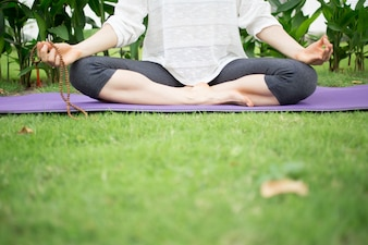 Low angle view of young woman meditating outdoors