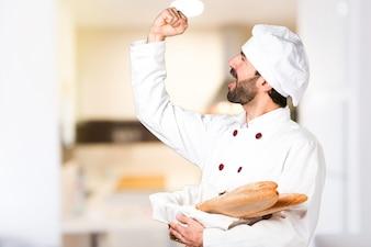 幸運な若いパン屋、キッチンにパンを持っている