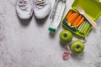 Lunch box with vegetables next to sneakers, water bottle and apples