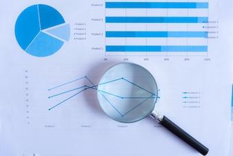 紙のグラフを持つ虫眼鏡。分析の概念