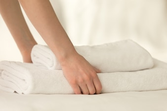 Maid placing stack of towels on the bed