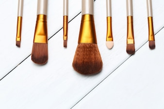 Make up brushes on wooden white desk