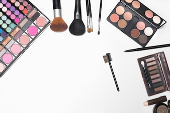 Makeup cosmetics and brushes on white background with copy space for text
