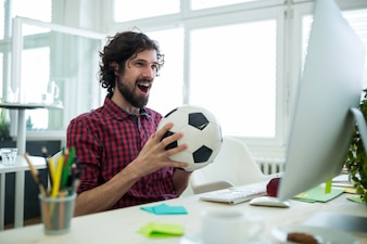 Male graphic designer cheering while watching football match