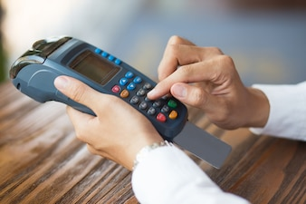 Male hands entering pin code on card reader