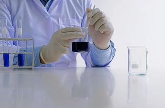 Male medical or scientific laboratory researcher performs tests with blue liquid in laboratory. Laboratory equipment and science experiments concept.