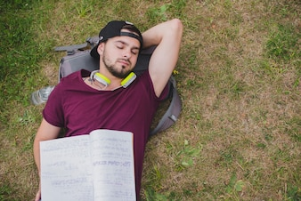 草の上に横たわっている男子学生スリープ