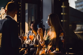 Man and woman drink cocktails in a street cafe on the summer terrace. Elegant couple drinks aperol spritz.
