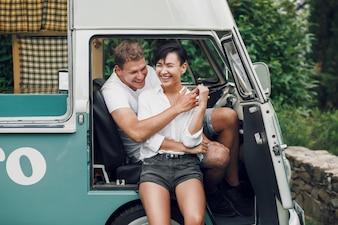 Мужчина и женщина обнимают и улыбаются, сидя в старом автобусе