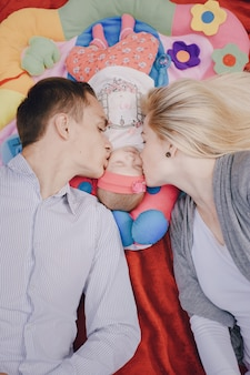 Man and woman kissing their baby