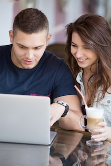 Man and woman looking a laptop