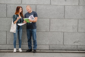 Man and woman standing against gray wall