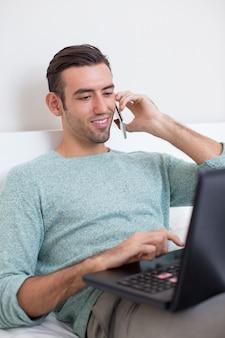 Человек, звонящий по телефону и работающий на ноутбуке дома