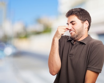 Man covering his nose with disgust