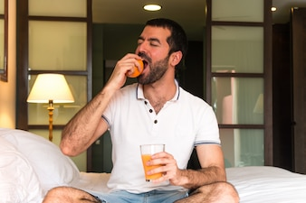 Man drinking orange juice in a hotel