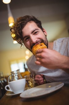 Man eating a croissant in café