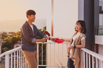 Man giving his girlfriend a heart-shaped box and a rose