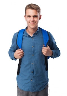 Man grabbing the grips of a blue backpack