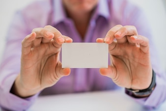 Man hand giving business card in office.