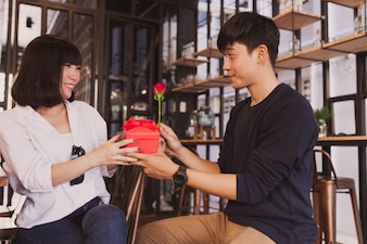 Man handing a gift to his girlfriend in a restaurant