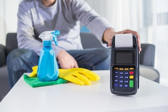 Man hold payment terminal besides spray bottle and rubber gloves