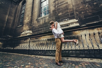 Man hold shis lady up kissing her before the church