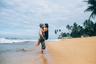 Man holding girlfriend and kissing on beach