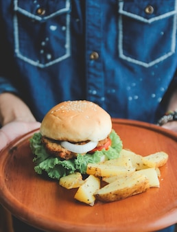 Man holding tasty burger on wooden tray