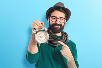 カラフルな背景にヴィンテージ時計を持つ男