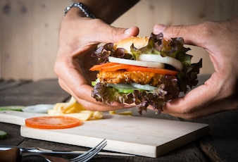 Man holds burger with hands and potato chip.
