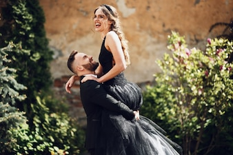 Man holds his smiling woman in black dress up