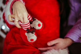 Man holds little red shoes on woman's belly