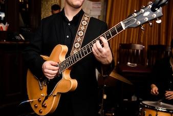Man in black shirt plays on guitar