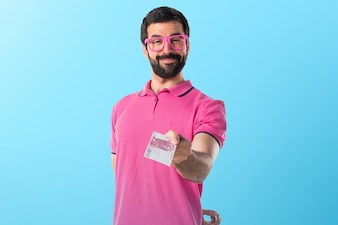 Man in colorful clothes taking a lot of money on colorful background