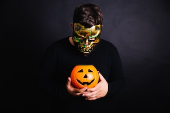 Man in gold mask holding pumpkin